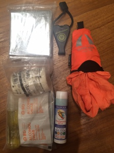 Emergency blanket, whistle, packable towel from Camp's Corner Singapore, sunscreen stick, and my first-aid kit