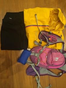 Yellow OMM Aeon Jacket, Nathan's Intensity Pack, packed blue Patagonia Houdini jacket, and Haglof waterproof pants